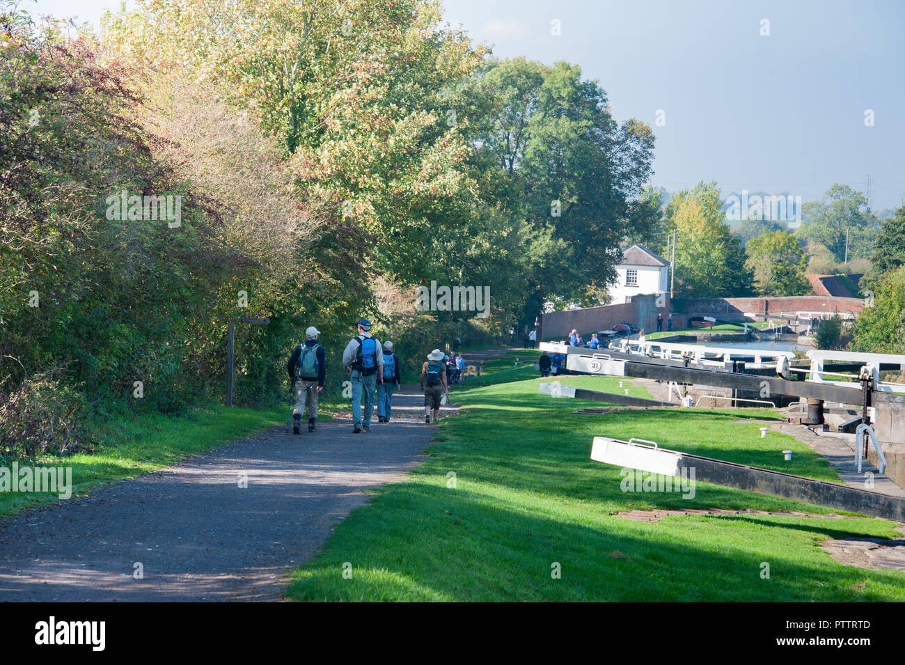 Walkers on the towpath at the Caen Hill Flight on the Kennet and Avon Canal, Devizes, Wiltshire, UK. - Stock Image