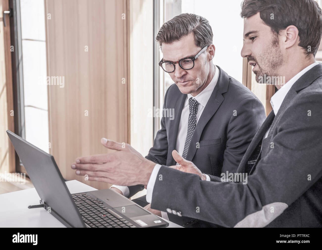 Zwei Maenner arbeiten an Laptop (model-released) - Stock Image