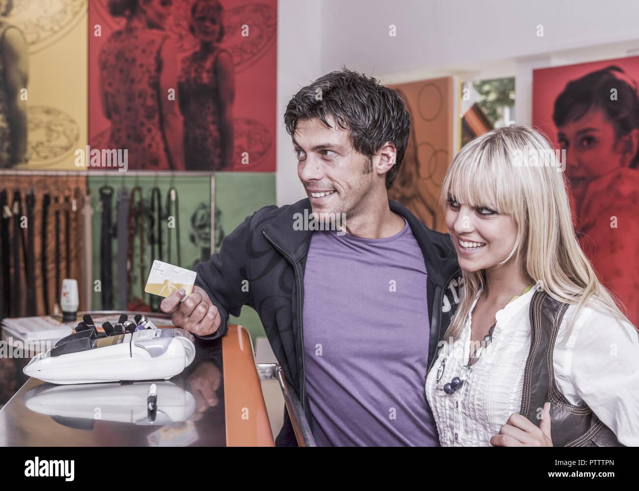 Paar in Boutique an Kasse, zahlen mit Karte (model-released) - Stock Image