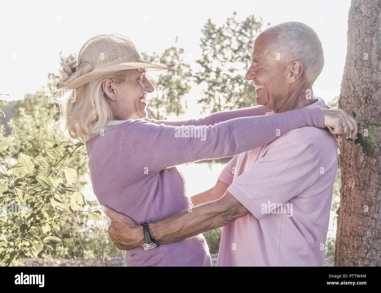 Seniorenpaar an See, umarmen sich lachend (model-released) Stock Photo