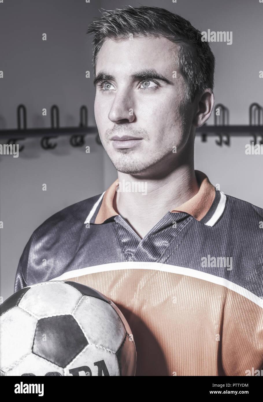 Fussballspieler mit Ball in Mannschaftskabine, Portraet (model-released) - Stock Image