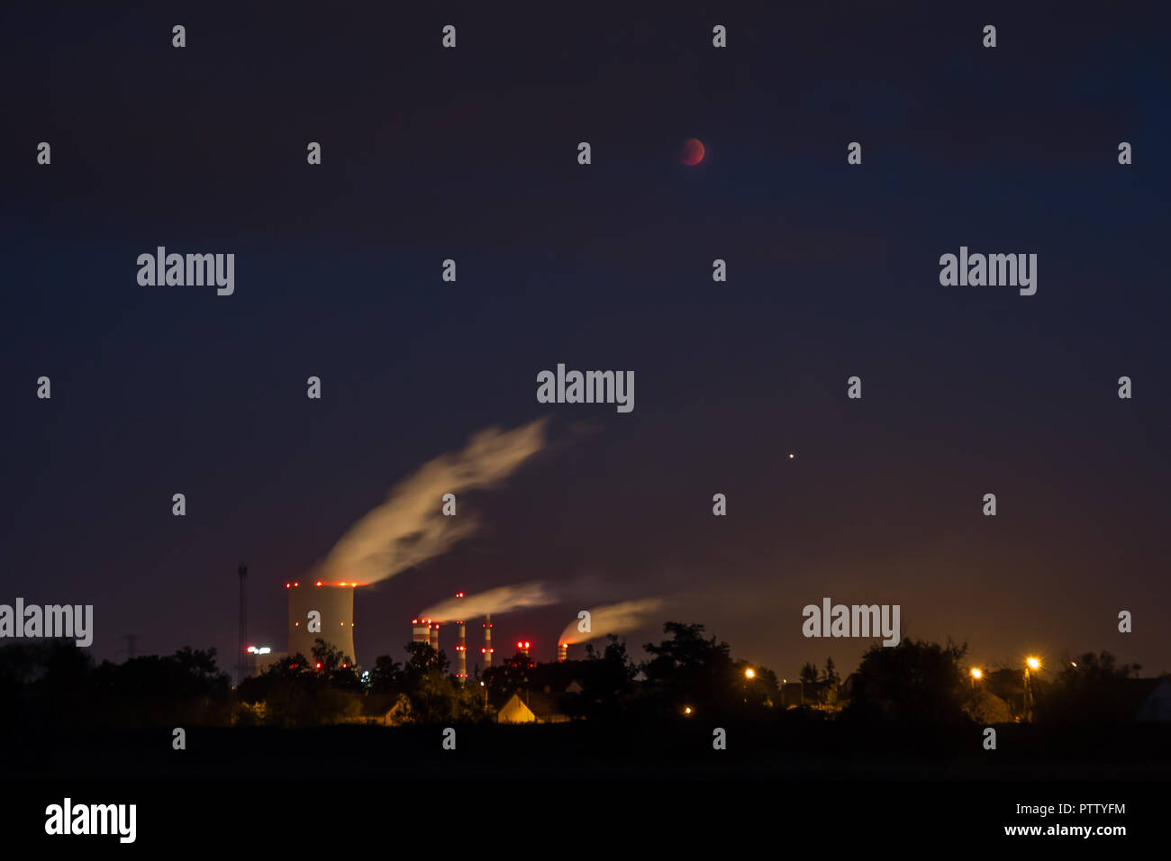 Moon total eclipse and mars over a large power plant Stock Photo