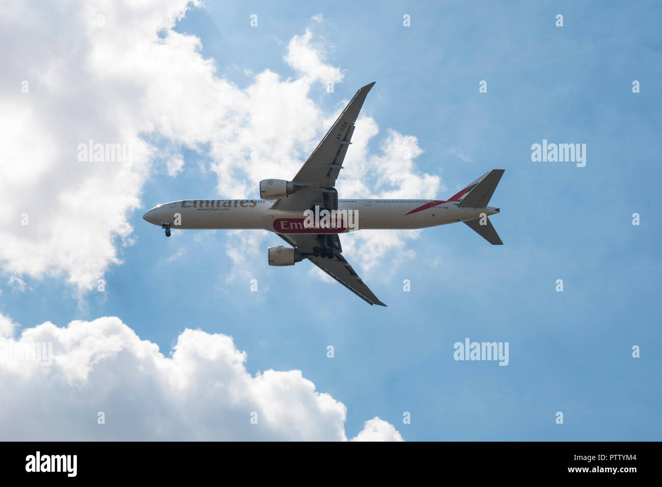 Emirates' Boeing 777 landing against blue sky and clouds Stock Photo
