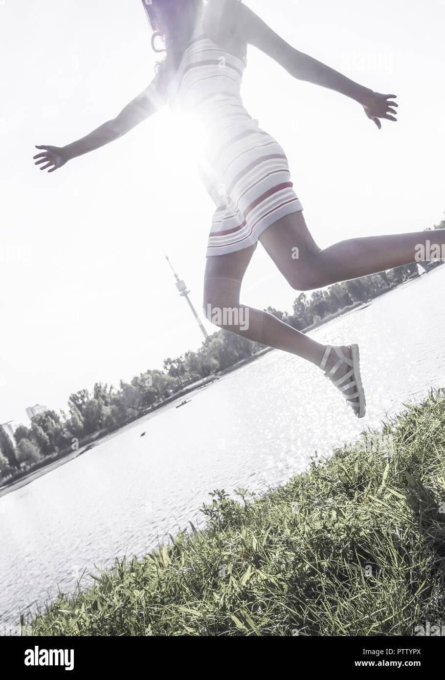 Frau spingt in die Luft, Gewaesser im Hintergrund (model-released) - Stock Image