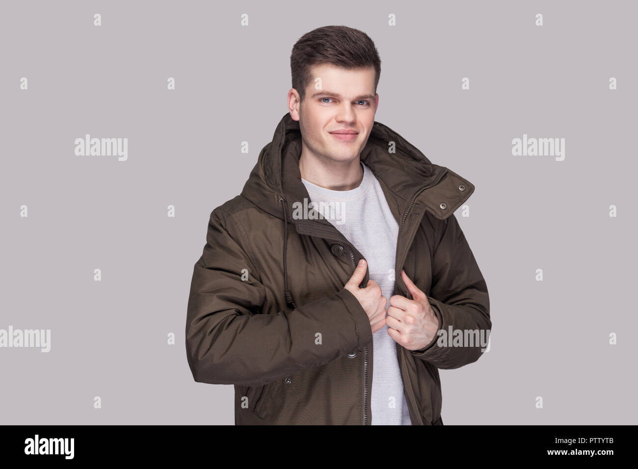 df844988c9458 Portrait of young handsome man standing in light gray shirt and dark green  parka looking at
