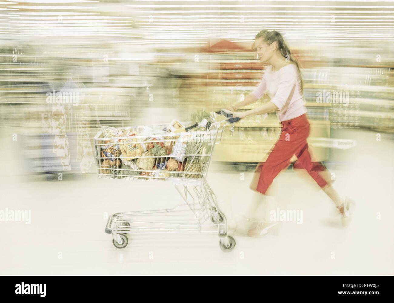 frau laeuft mit einkaufswagen durch supermarkt bewegung model released stock photo 221825469