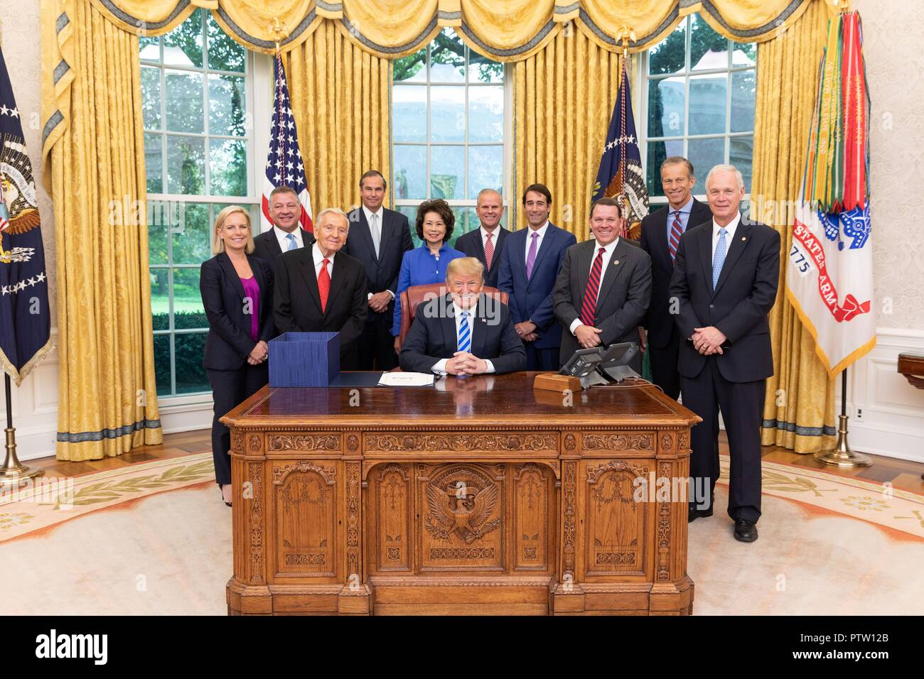 U.S President Donald Trump poses with members of Congress and his cabinet after signing H.R. 302, the FAA reauthorization Act of 2018 in the Oval Office of the White House October 5, 2018 Washington, DC. - Stock Image