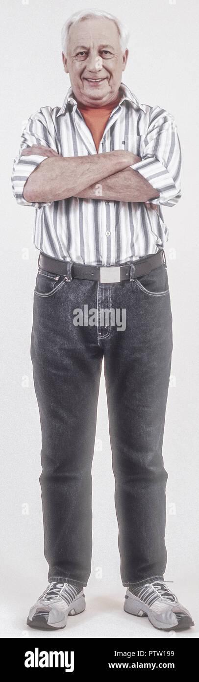 Senior in Jeans und Hemd, verschraenkte Arme (model-released) Stock Photo