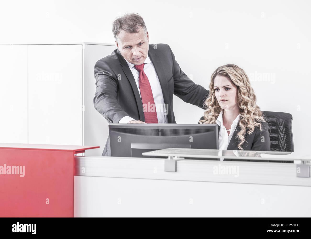 Mann und Frau schauen auf Bildschirm (model-released) - Stock Image