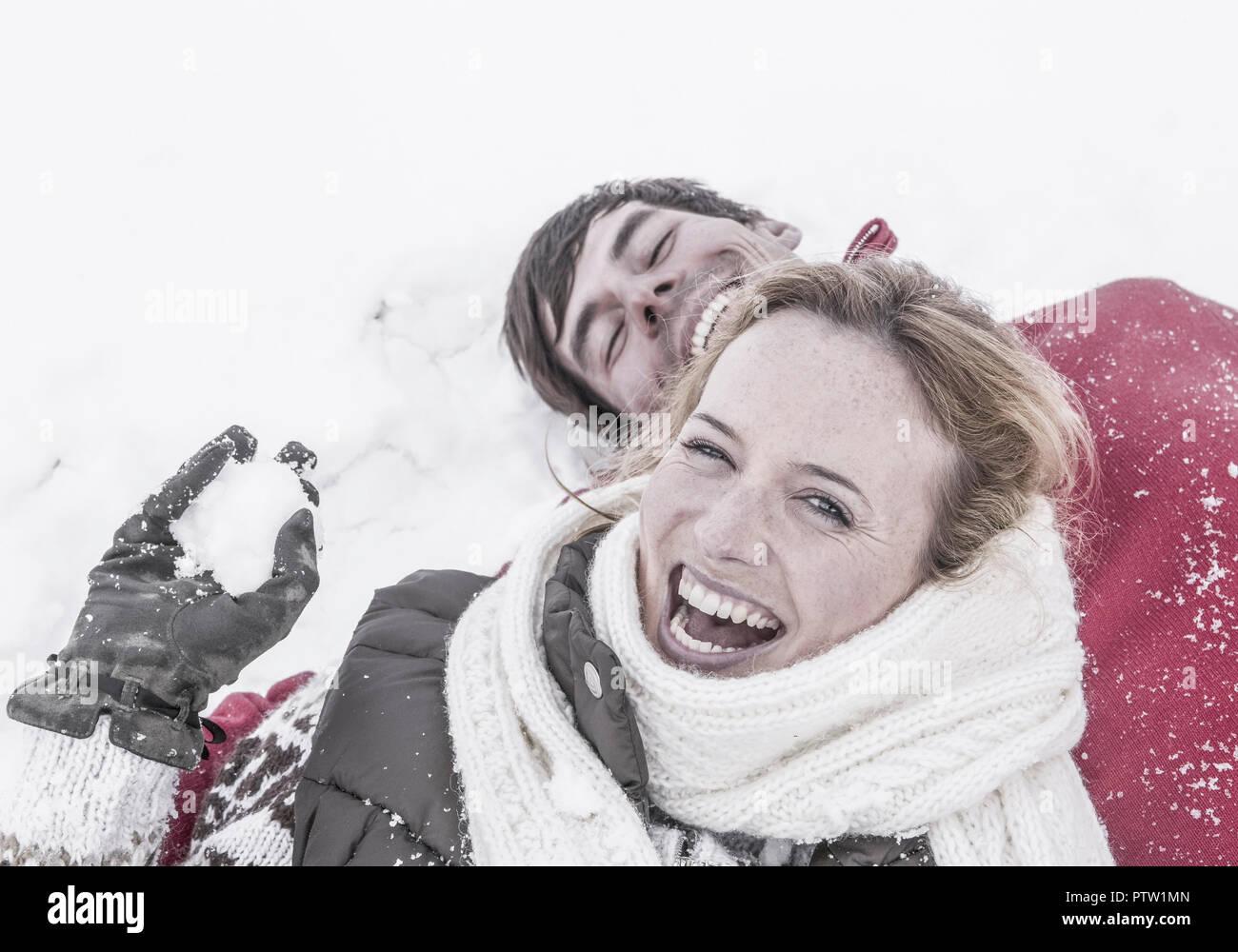 Paar im Winter, liegen lachend im Schnee (model-released) Stock Photo