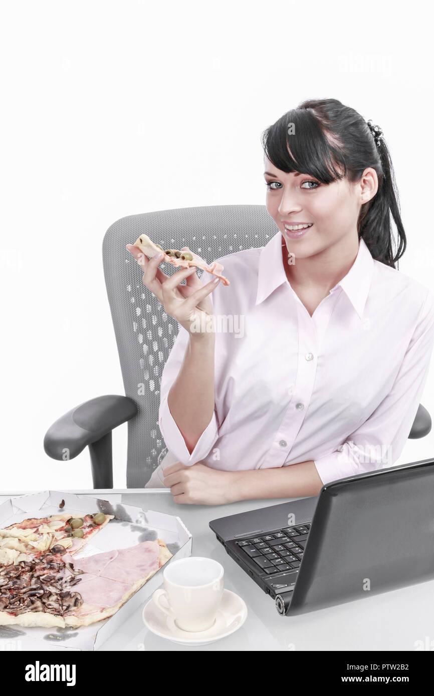 Junge Frau isst Pizza im Buero, Businesswoman eating pizza in the office (Modellfreigabe) Stock Photo