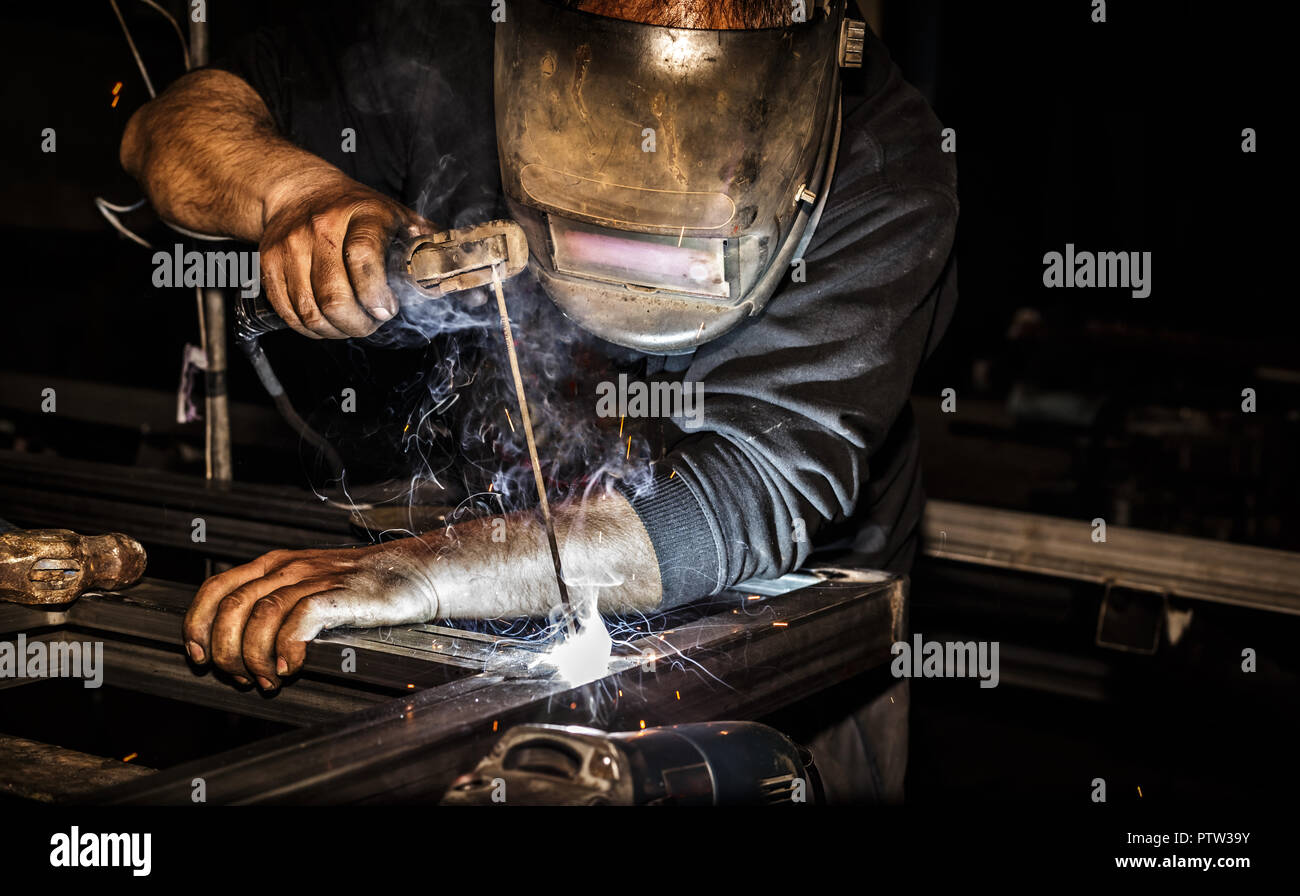 Professional welder in mask welds steel with electric torch tool - Stock Image