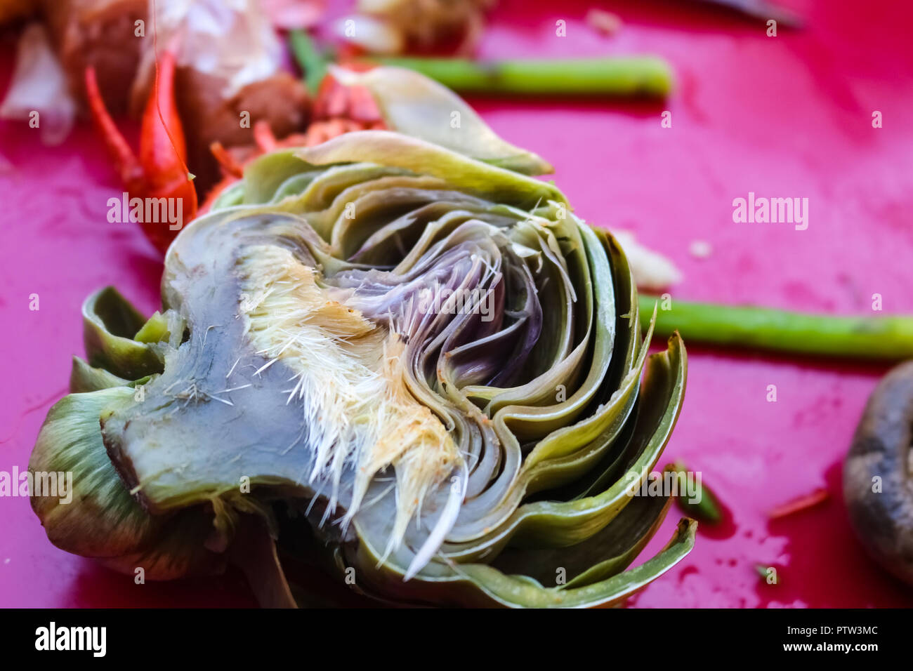 Boiled artichoke cut in half lying on pink tablecloth with mushroom and asparagus at crawfish boil - selective focus Stock Photo