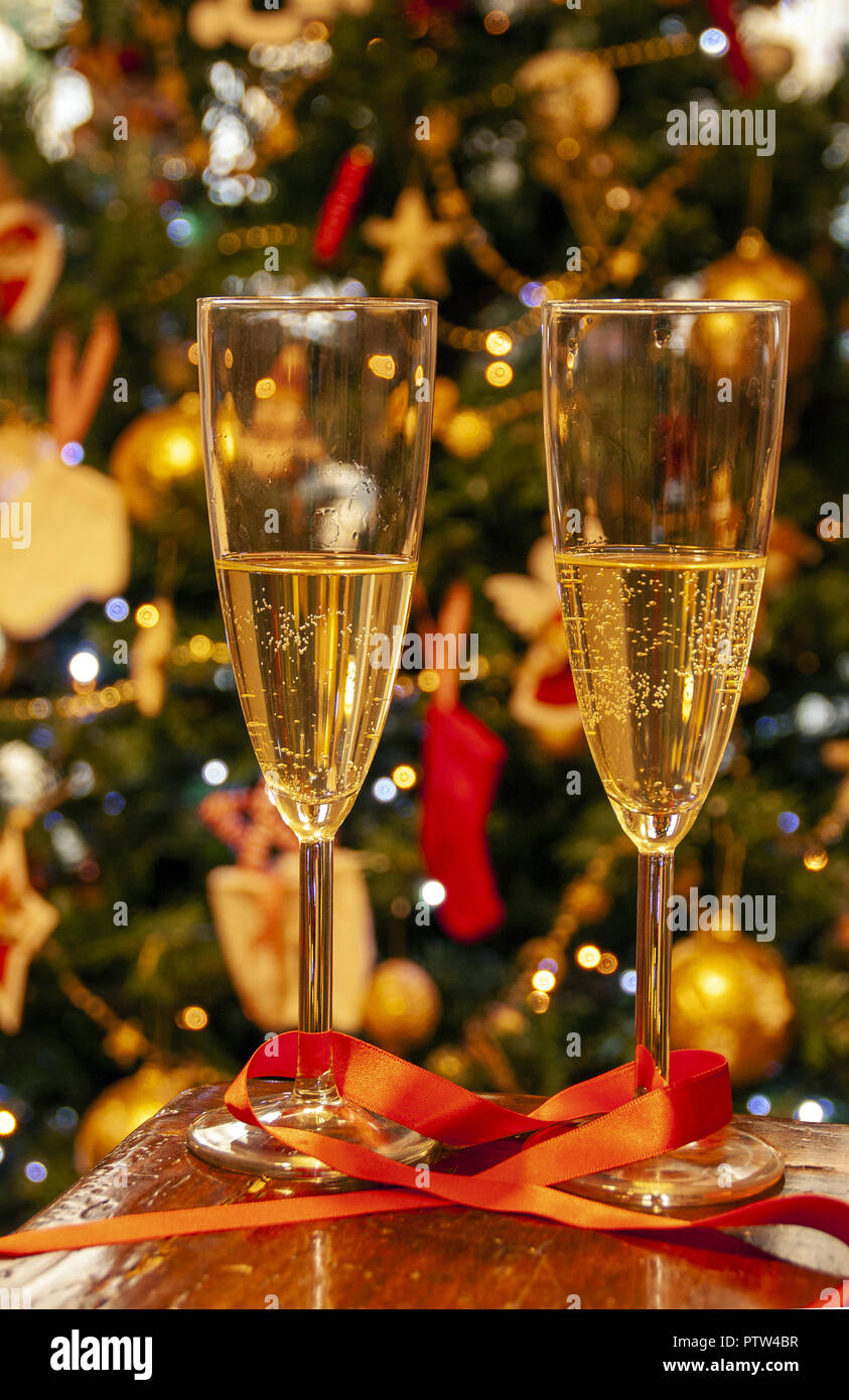 new year celebration two flutes of champagne on the background of christmas lights and tree