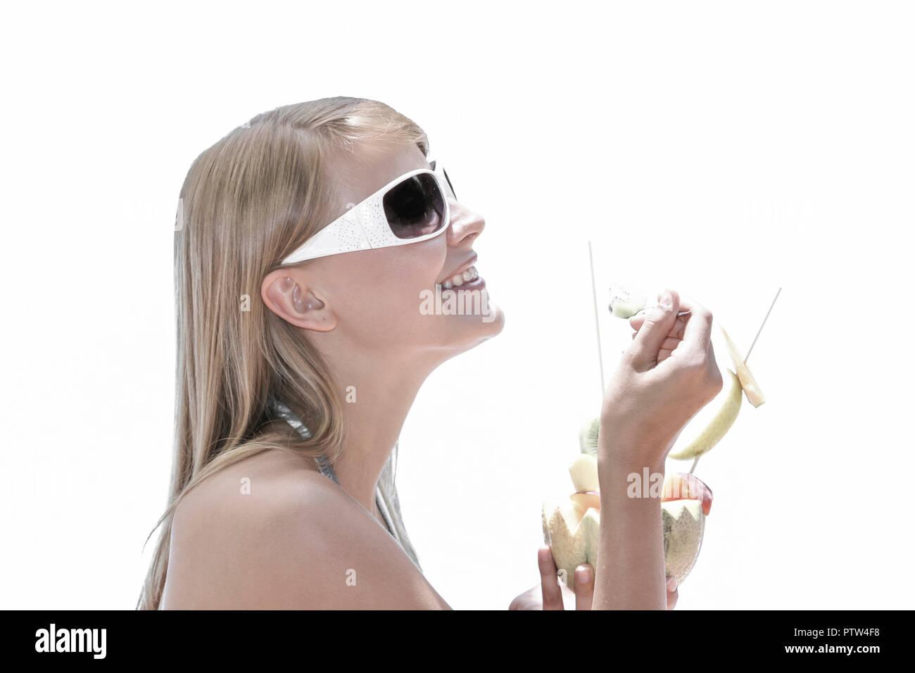 Blonde Frau geniesst einen Fruchtcocktail im Sommerurlaub am Pool, Portrait (Modellfreigabe) - Stock Image