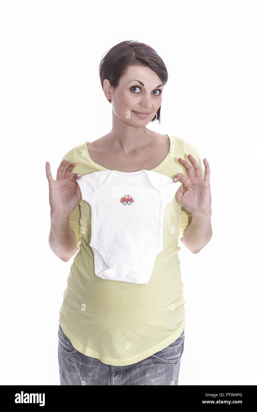 Schwangere Frau in freudiger Erwartung zeigt Babybekleidung (Modellfreigabe) - Stock Image
