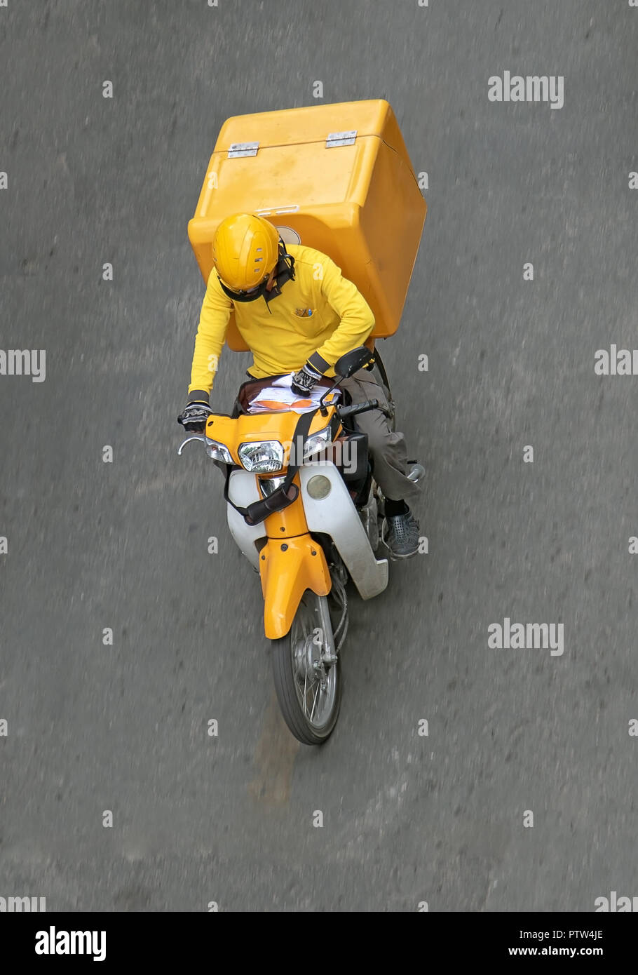Delivery of consignments on motorbike. Motorcyclist rides with delivery in the large yellow box on street Ho Chi Minh city - Stock Image