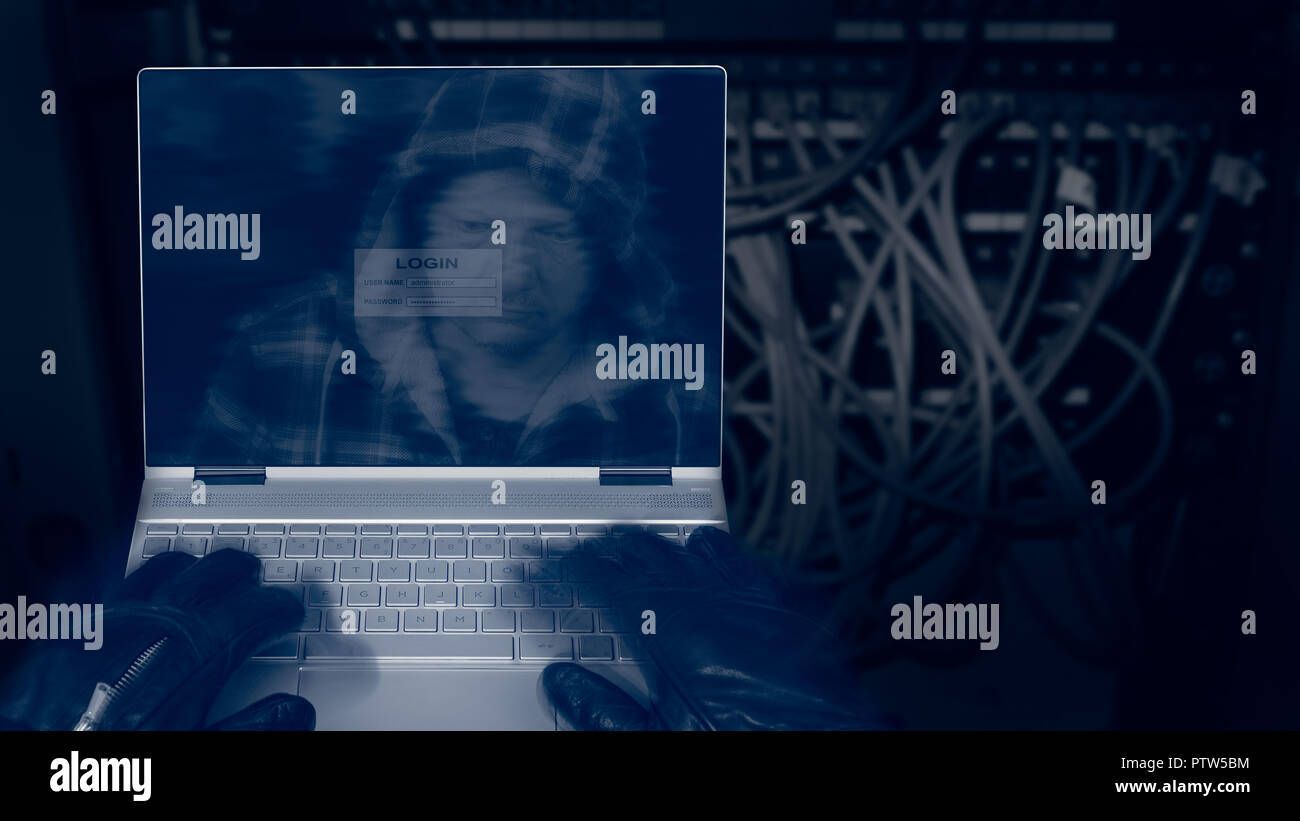 Hacker with laptop on a dark background of structured cabling. Close-up of male hands in black gloves on keyboard, motion blur. Spy's head in hood. - Stock Image