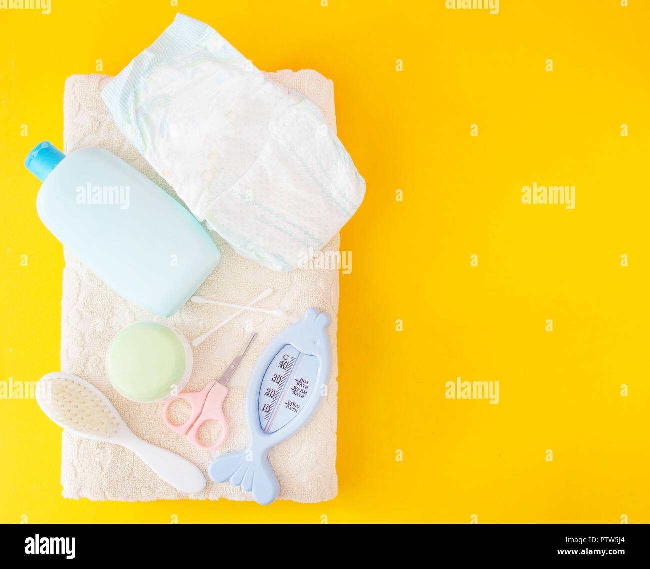 Baby bathing accessories, diaper, yellow background Stock Photo