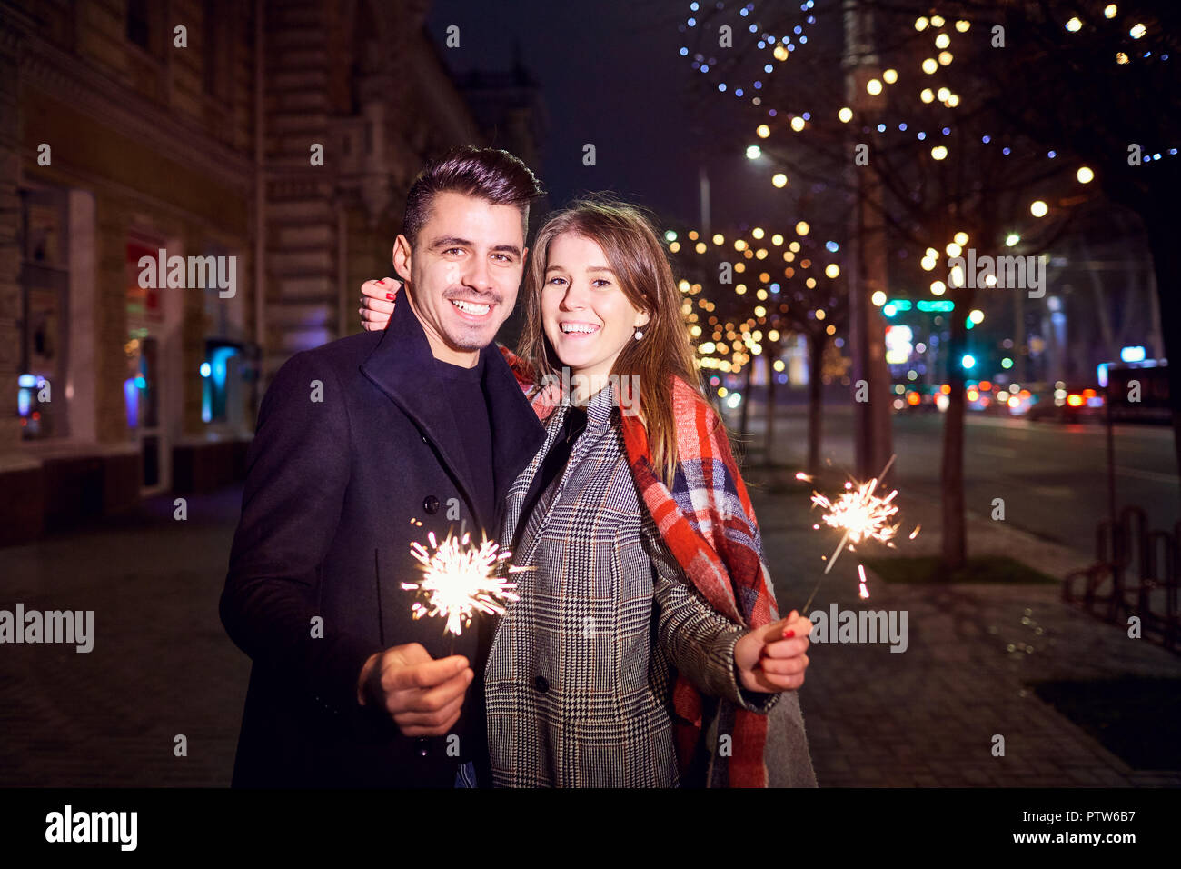 A young couple with sparklers in the hands at Christmas. - Stock Image
