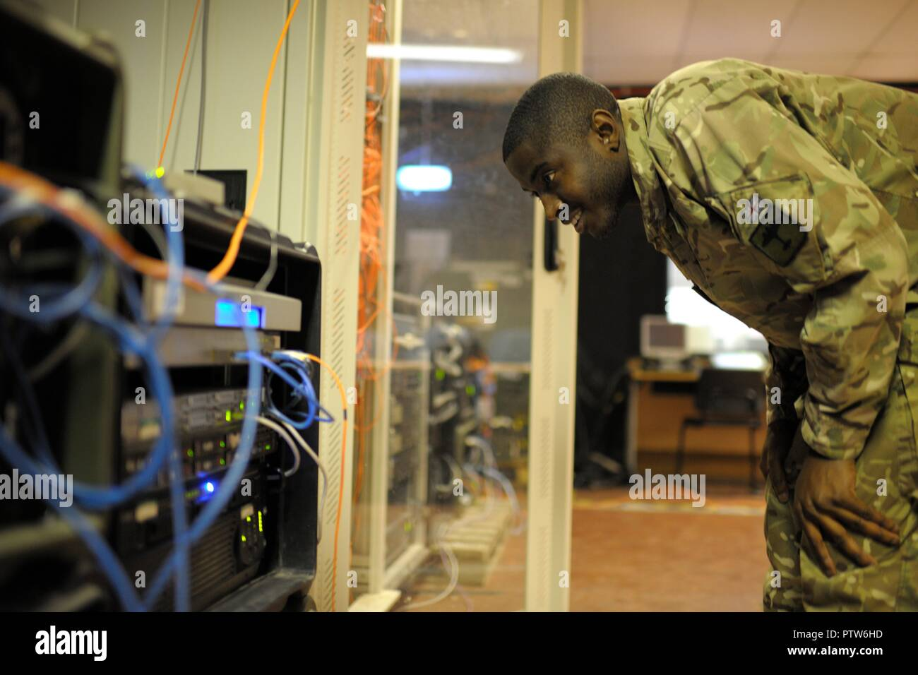 British Army soldier checks computer server equipment - Stock Image