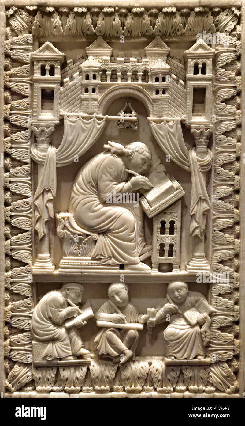 A ninth-century Carolingian carved-ivory relief depicting St Gregory (Pope Gregory I) writing with the Holy Ghost, in the form of a dove (his attribute), imparting the word of God to the saint, which is taken down by scribes. - Stock Image