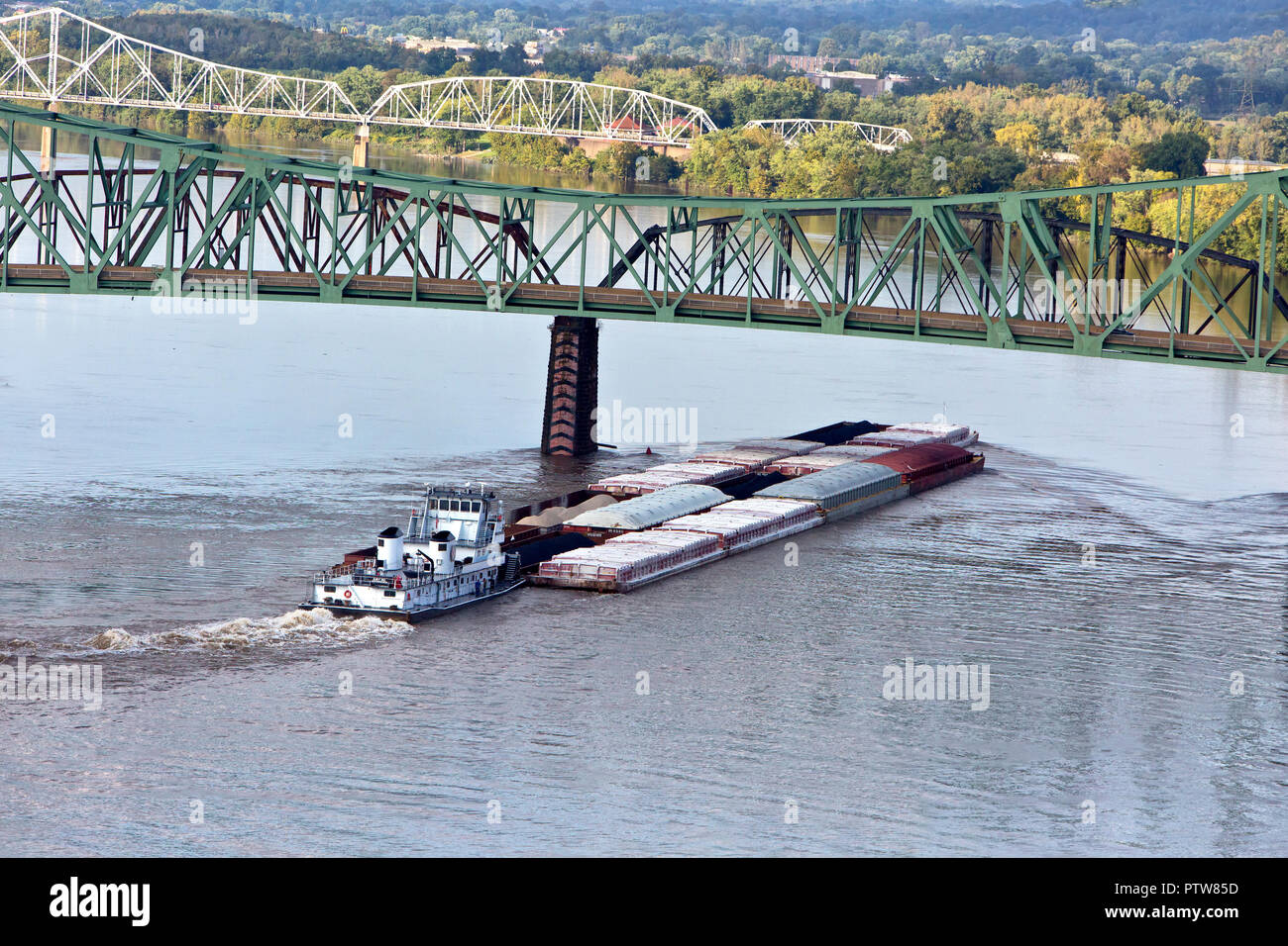 Tugboat 'Allen P. Hall' pushing barges loaded with various covered products including coal, Parkersburg-Belpre cantilever bridge. - Stock Image