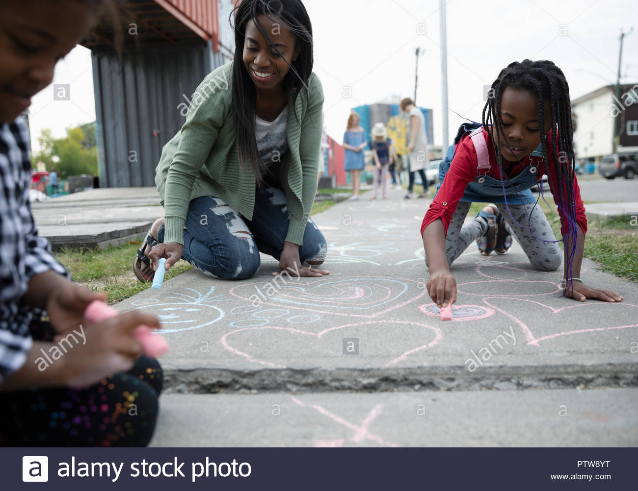 Mother and daughters coloring with sidewalk chalk - Stock Image