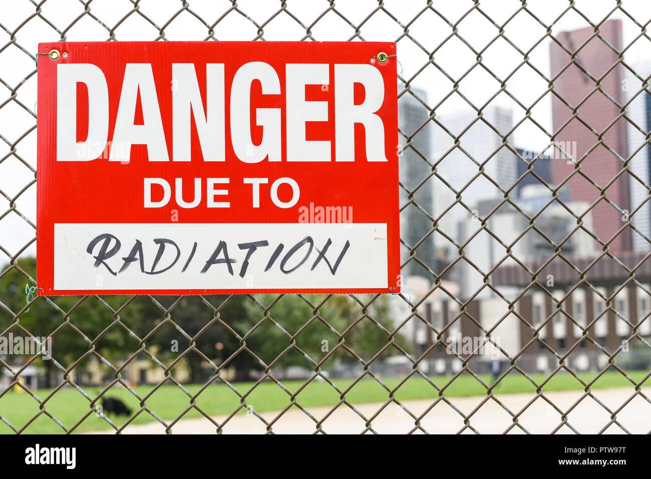 Sign danger due to radiation attached on the fence in the front of the town - Stock Image