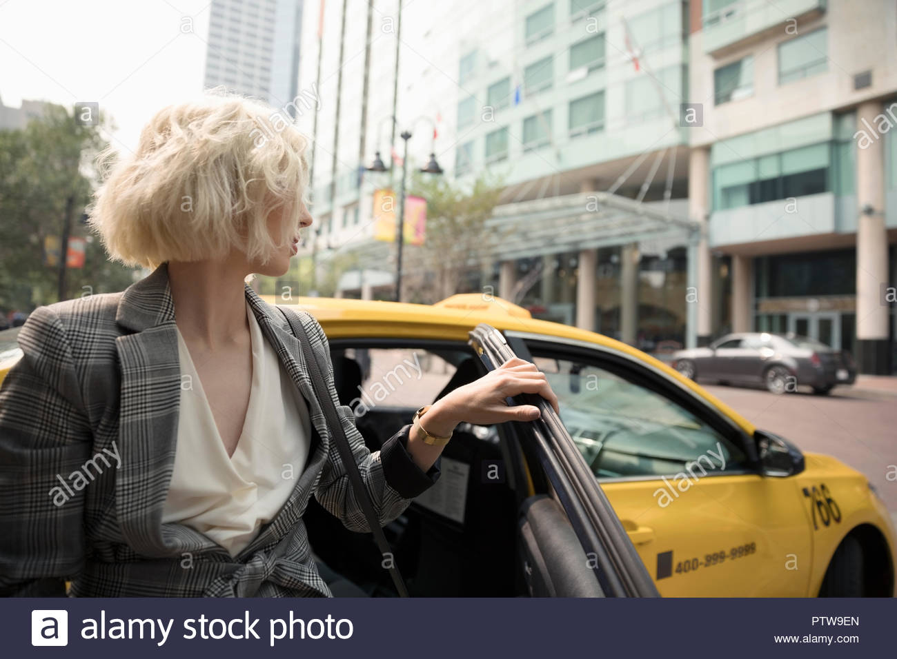 Young businesswoman getting out of taxi on urban street - Stock Image