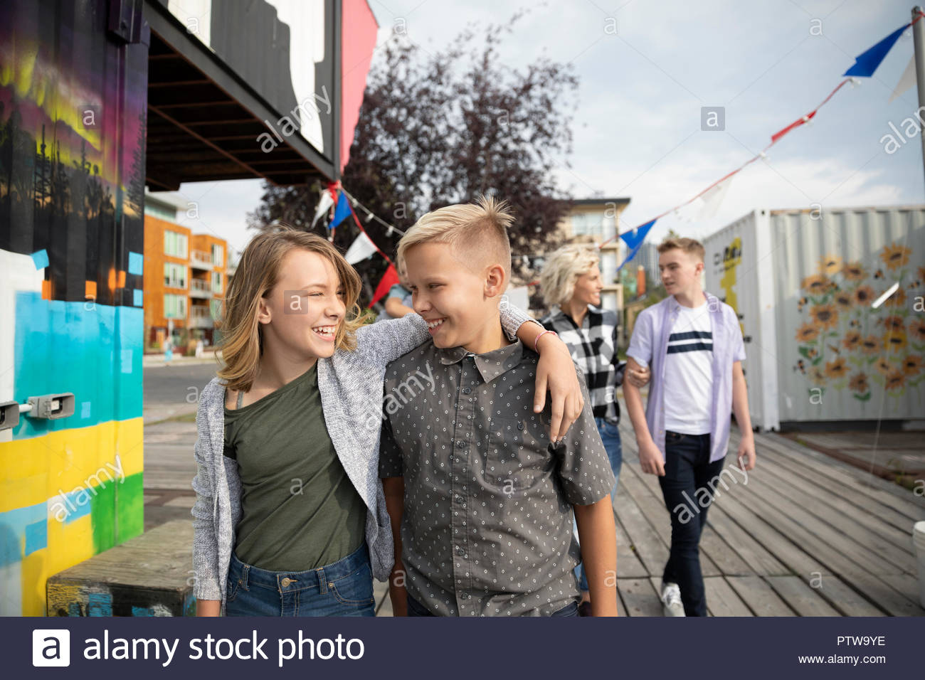 Affectionate brother and sister walking at carnival - Stock Image