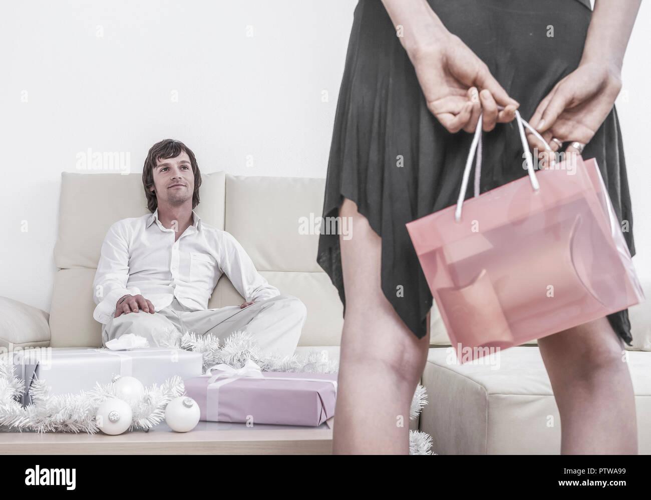 Paar, Mann sitzt auf Sofa, Frau steht mit Geschenktuete davor (model-released) Stock Photo