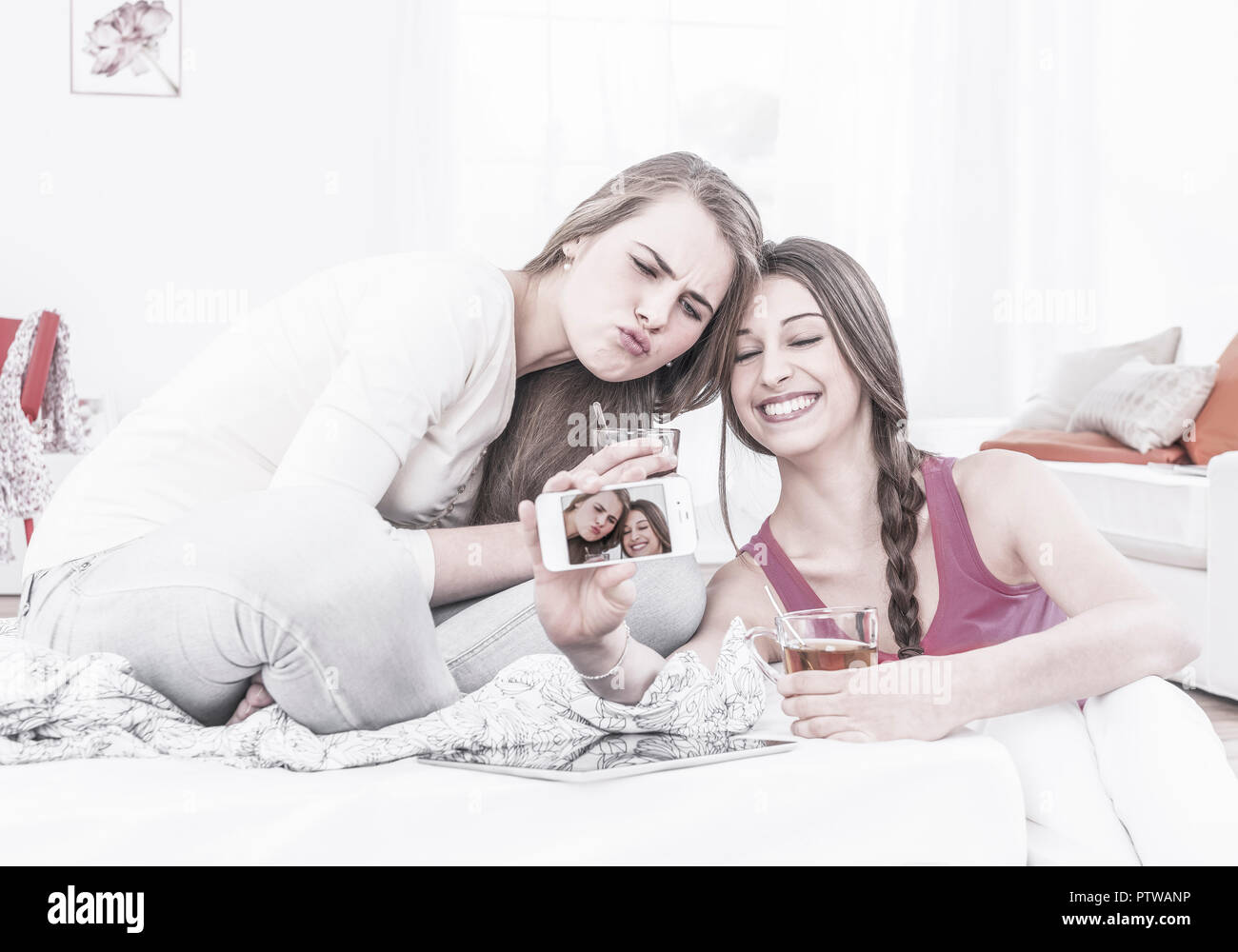 Zwei Maedchen fotografieren sich mit Smartphone (model-released) - Stock Image