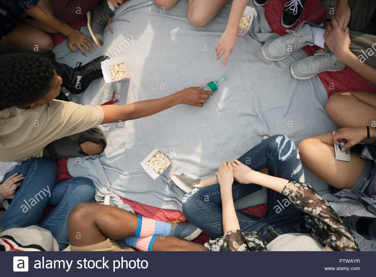 Teenage friends hanging out, playing spin the bottle - Stock Image