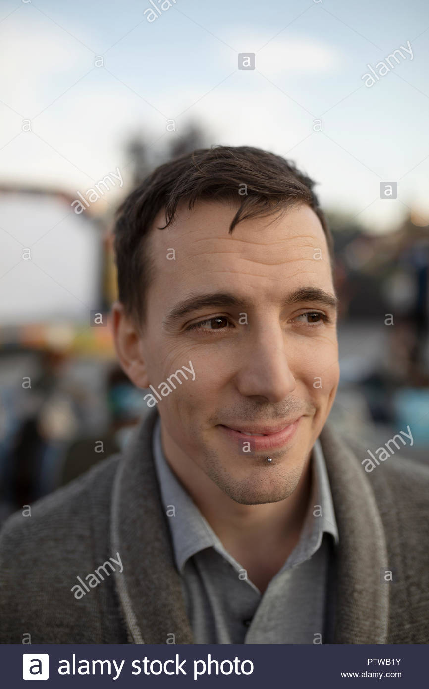 Portrait smiling man with chin piercing looking away - Stock Image