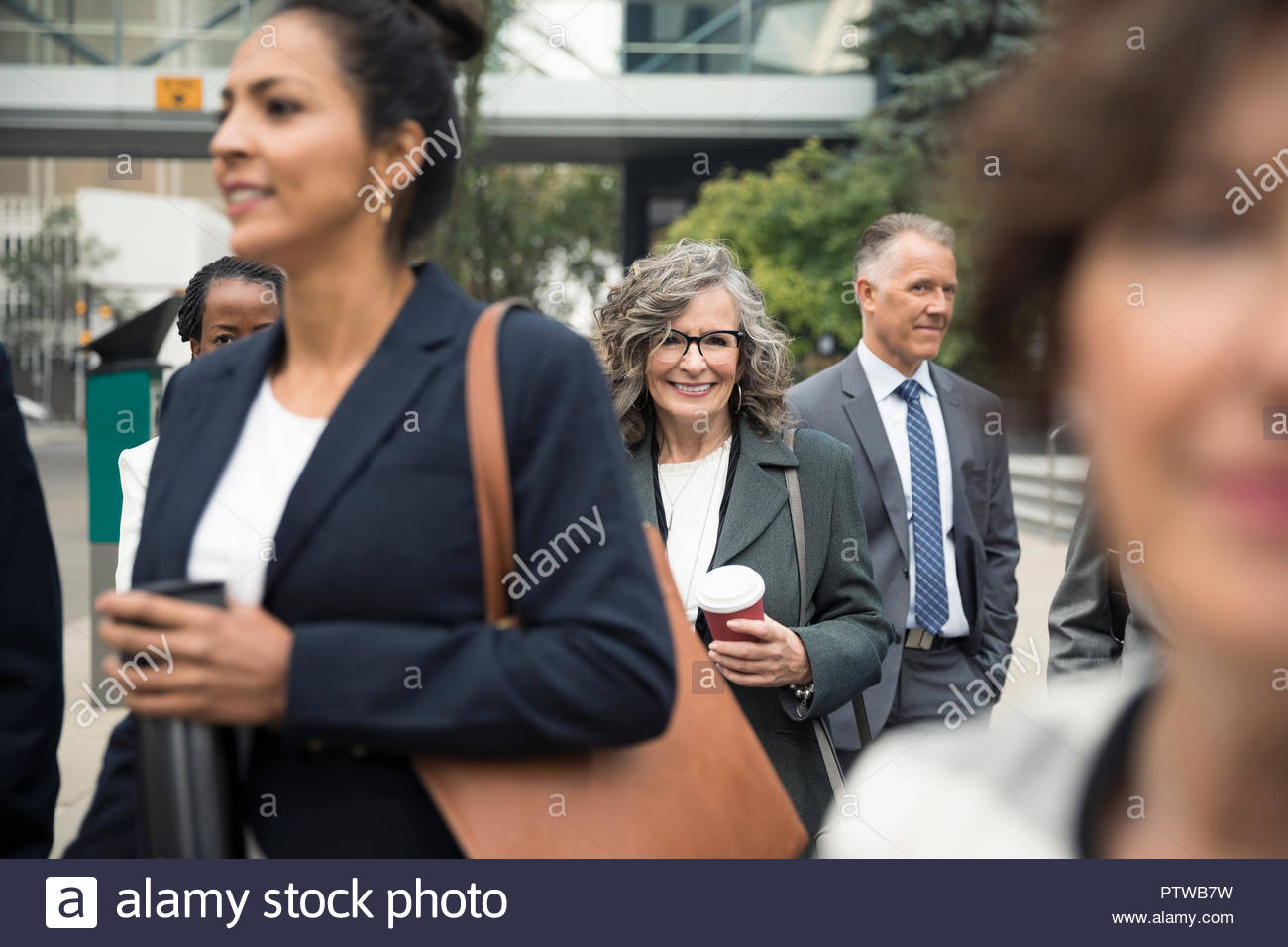 Confident senior businesswoman with coffee among business people on urban sidewalk - Stock Image