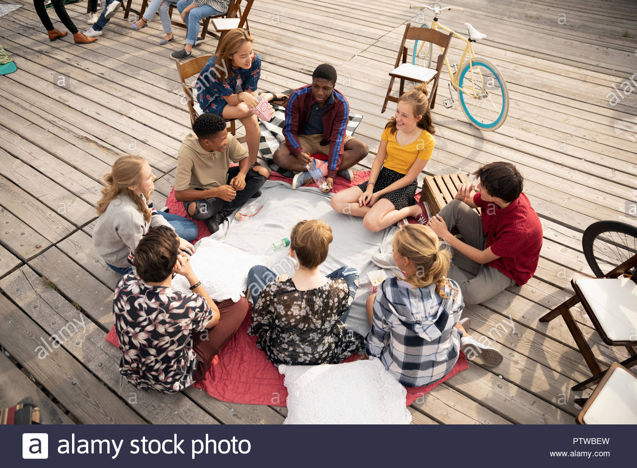 Teenagers hanging out, playing spin the bottle - Stock Image