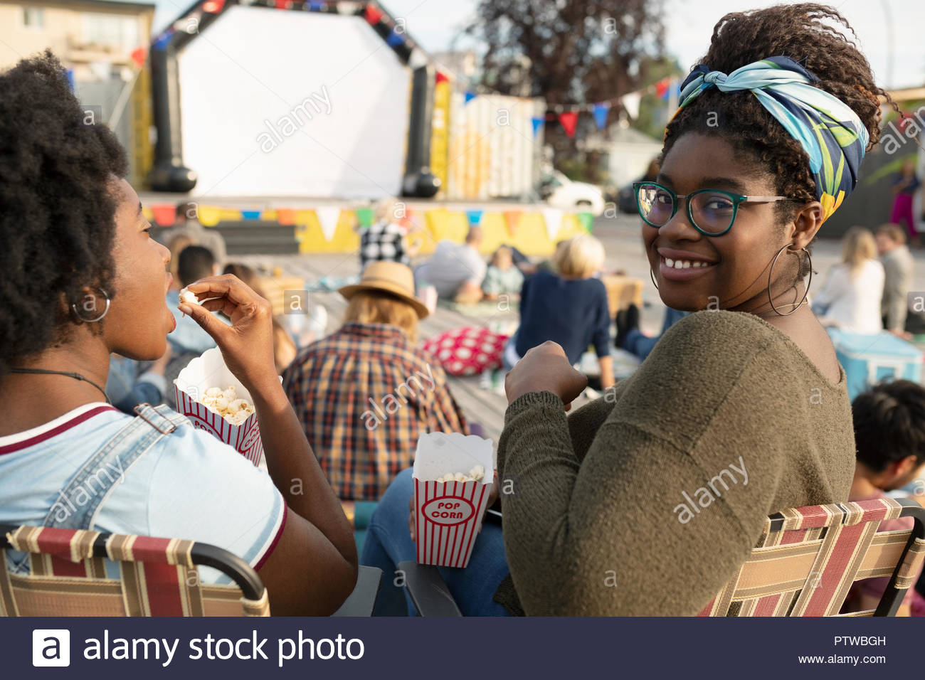 Portrait smiling young woman eating popcorn, enjoying movie in the park - Stock Image