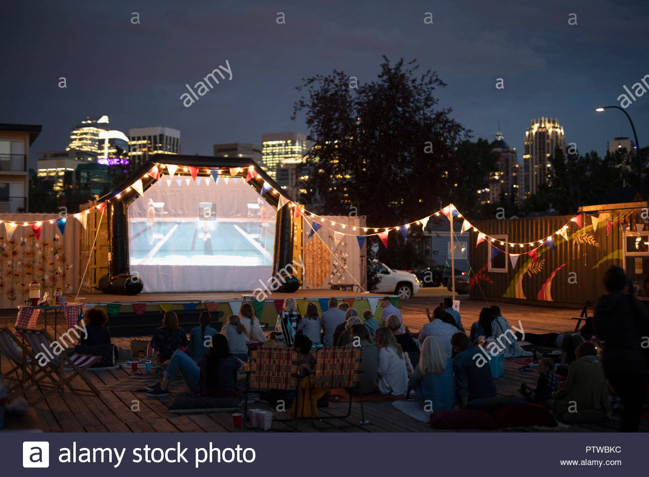 Crowd enjoying movie in the park in urban park - Stock Image