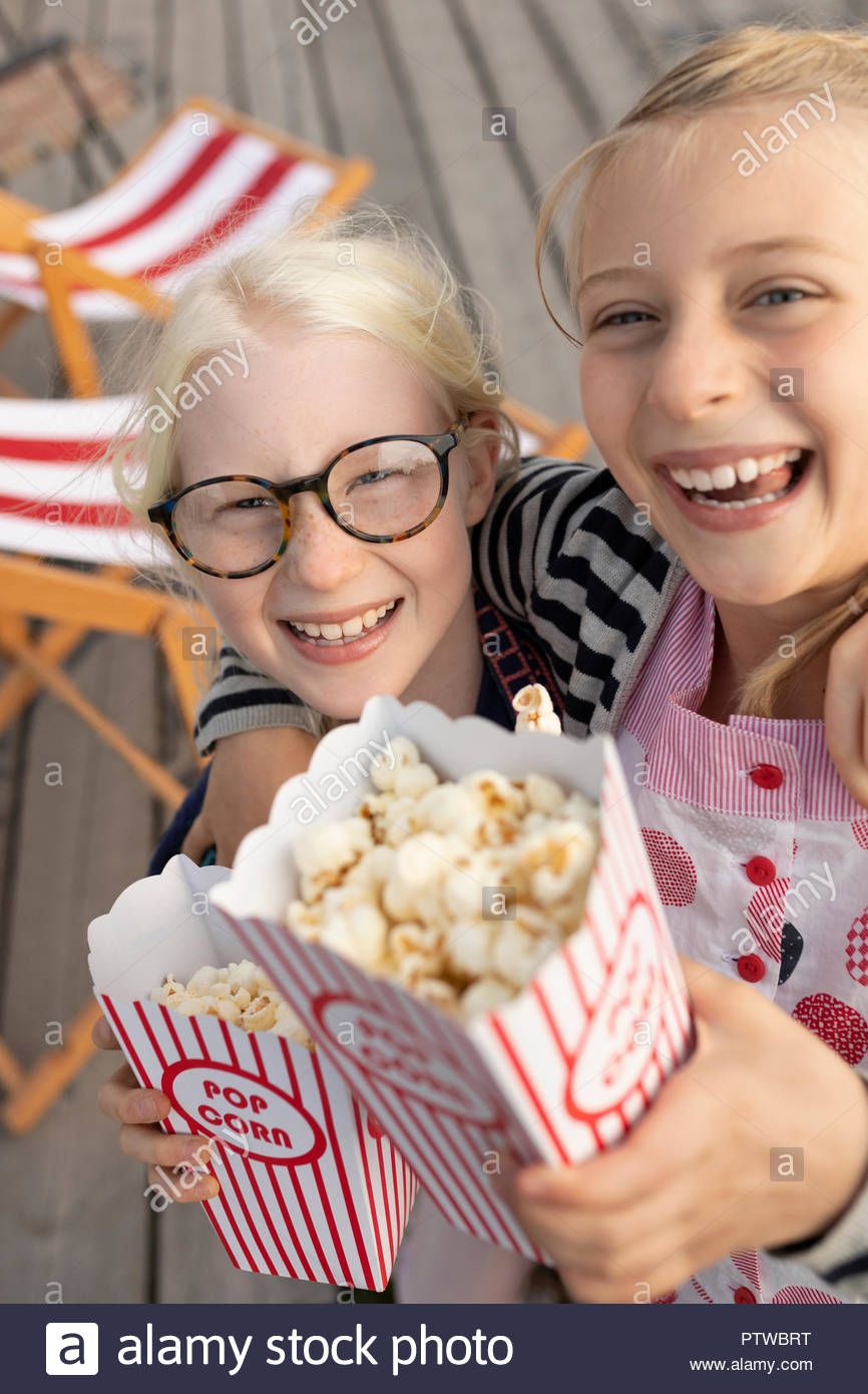 Portrait smiling, enthusiastic sisters with popcorn - Stock Image