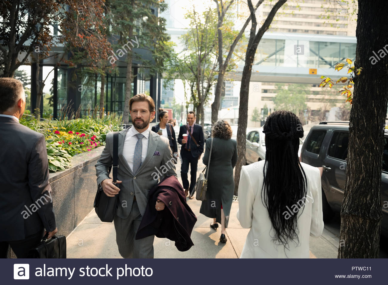 Business people walking on city sidewalk - Stock Image