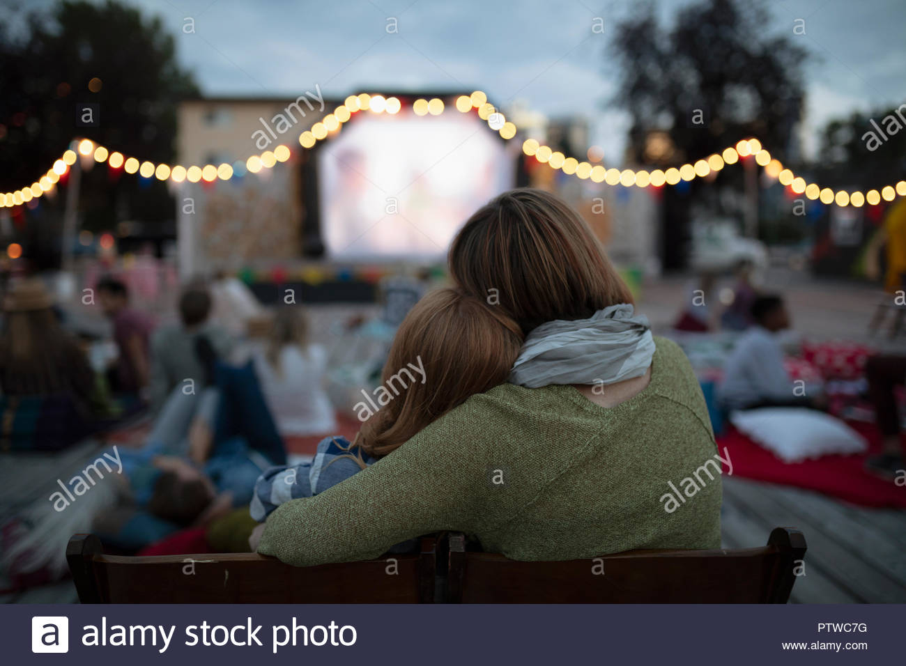 Affectionate mother and daughter at movie in the park - Stock Image