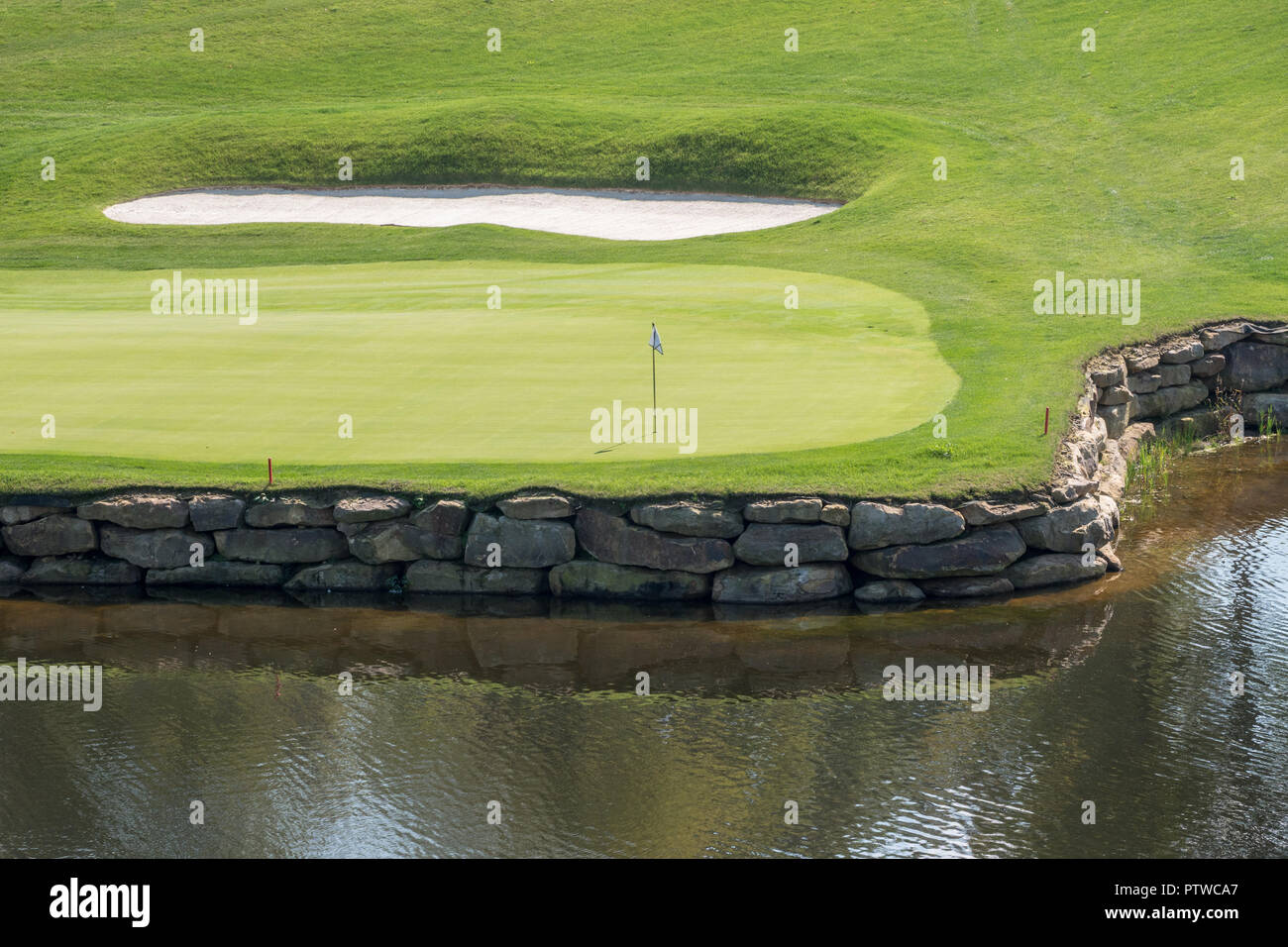 Challenging hole on luxury golf course with water and sand - Stock Image
