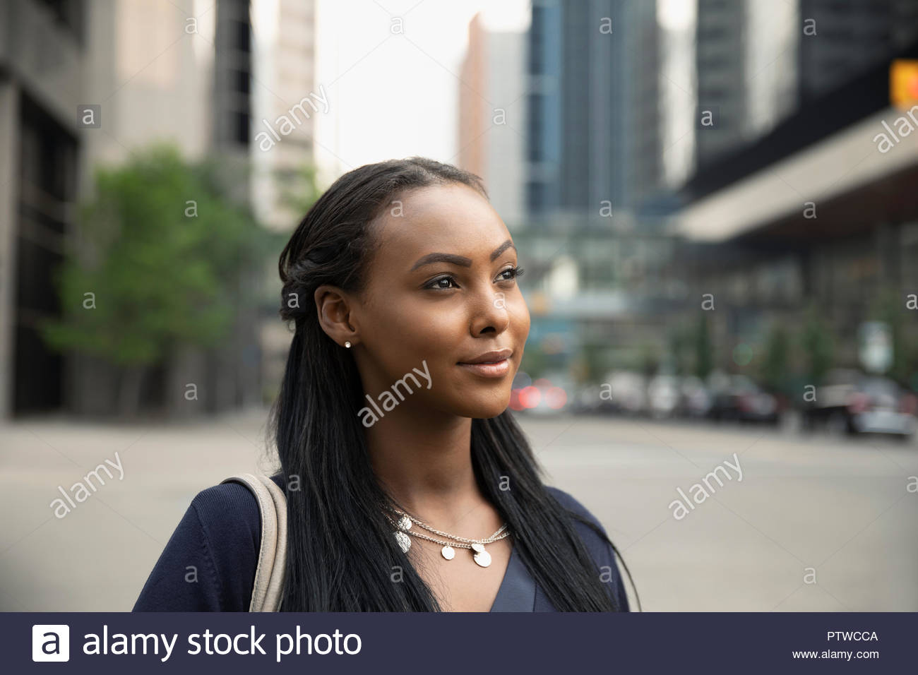 Confident, thoughtful, forward looking young woman on urban street - Stock Image