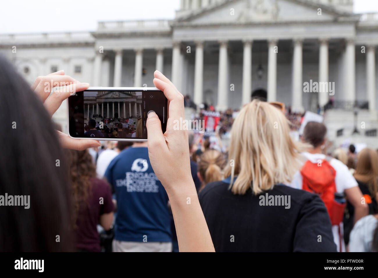 Woman taking photos of political protest using a mobile phone (iPhone) - USA - Stock Image