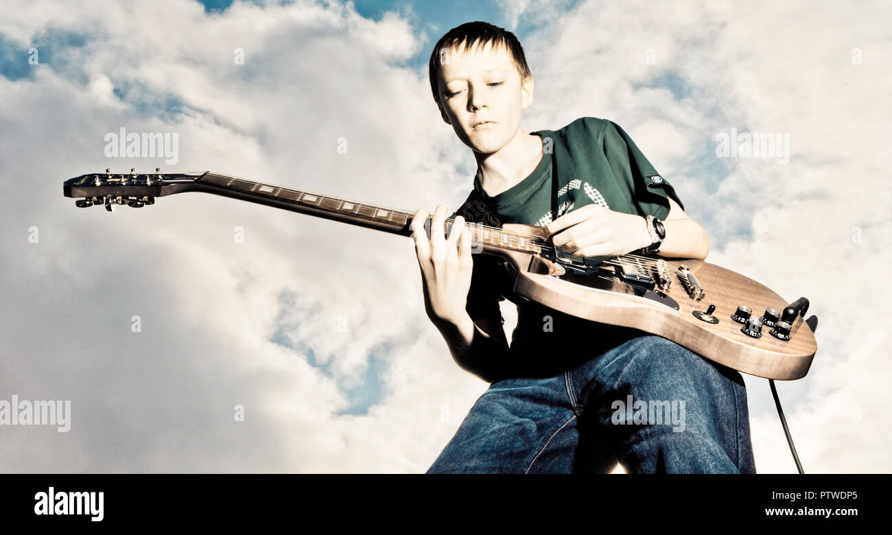 Left handed boy plays electric guitar outside with sky as his audience - Stock Image