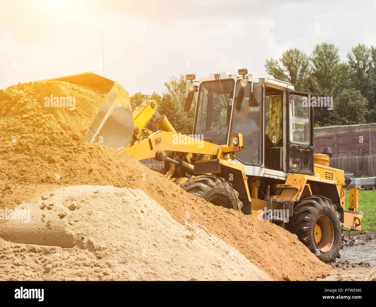 Yellow tractor loader is picking up a bucket of earth, mechanical, ladle with earth and sun Stock Photo