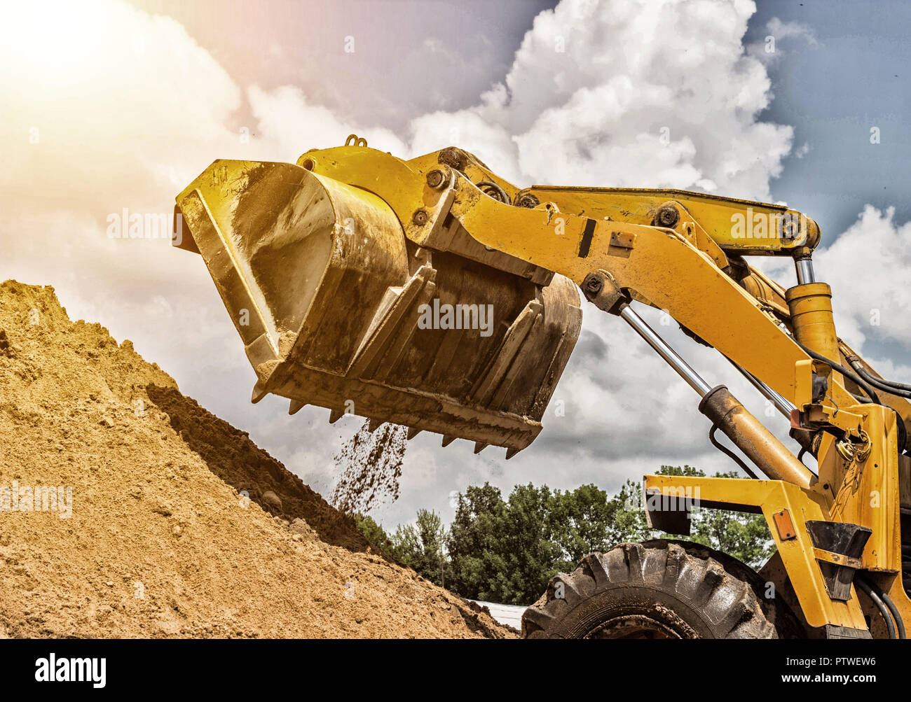 Yellow forklift lifted bucket on a pile with earth, blue sky and sun Stock Photo