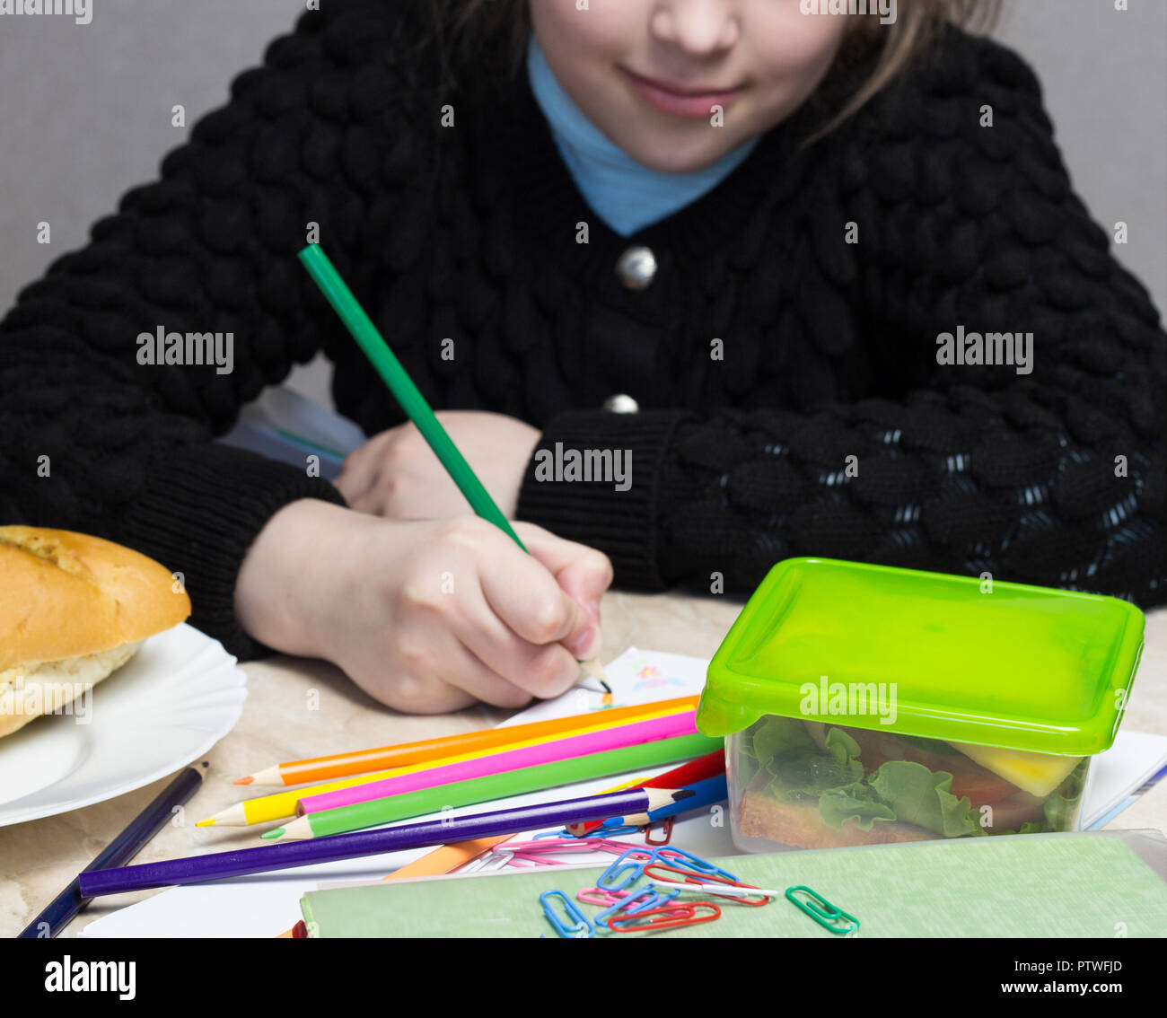 the girl does the lessons, on the table lies a sandwich, fruit, nuts, textbooks, pencils, nosh - Stock Image