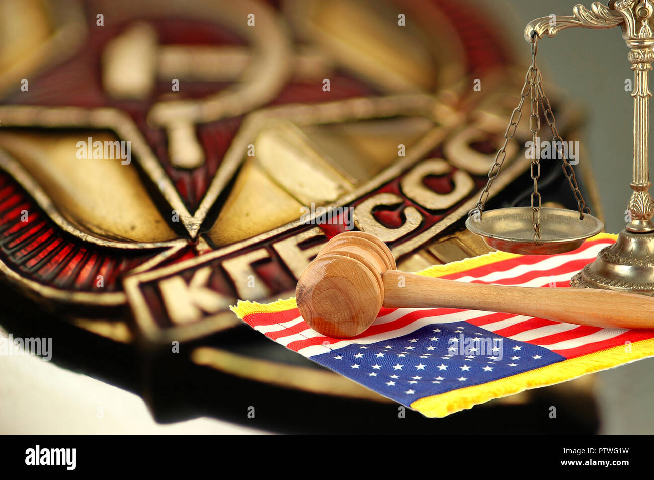 scales of justice, wooden gavel and United States flag on background with coat of arms of the state security Committee of the USSR (KGB) - Stock Image
